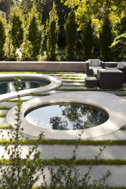 By adding horizonal bands of blue stone and grass, the design accentuates the curves of the existing pools. A few steps below, angular slabs of concrete leads to a seating area with an outdoor fireplace. Photography by Keller + Keller