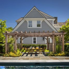 The cedar pergola is centered between the pool and residence providing additional outdoor seating for family entertaining. Photography by Anthony Crisafulli