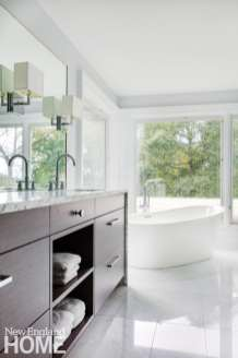 Large windows frame a soaking tub in the spa-like master bath, letting the outdoors in.