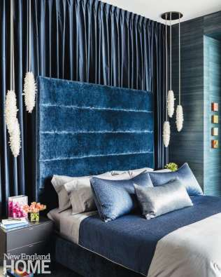 To match the bold blue of the master bedroom, the designer went with high-gloss lacquered bedside tables with frosted-glass tops.