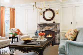 In the parlor, the owners' existing furnishings were reupholstered and paired with a generous coffee table. The new fireplace surround was fashioned from arabescato grigio orobico marble, which picks up the coral in the curtains; doors to the right conceal storage. The seagrass carpet provides an organic counterpoint to the formal furnishings.
