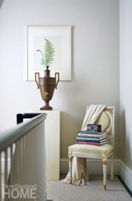 A 200-year-old urn is paired with a Louis XVI chair on the landing outside the master suite, which occupies the entire second floor.