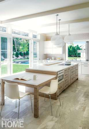 The indoor-outdoor connection is evident in the open kitchen, where painted perimeter cabinets with full overlay doors set the clean-lined tone, while fumed gray veneers on the island offer contrast.