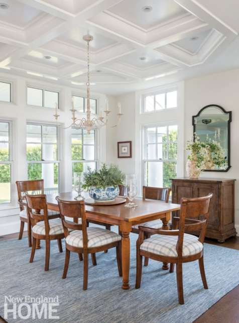 A distressed cast-iron chandelier hangs from a coffered ceiling in the English country dining room.