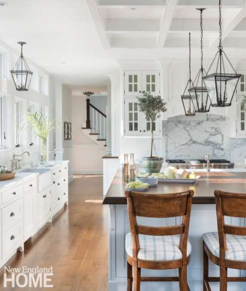 Stools patterned after traditional English high-backed chairs sit before the vast mahogany-topped kitchen island, with fabric patterns repeated from the adjacent dining room.
