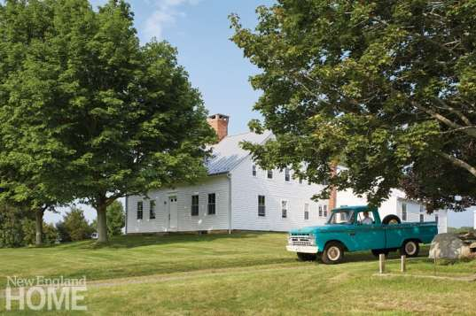 The 250-year-old farmhouse appealed to owner Michael Quadland, shown here in his 1966 Ford pickup, for its rural location, its simplicity, and its sense of permanence.
