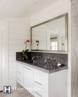 A concrete countertop and backsplash are accented with wall mount faucets and double sinks.