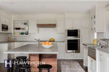 Crisp white kitchen cabinets are mixed with walnut, stainless steel and hand-crafted subway tiles.