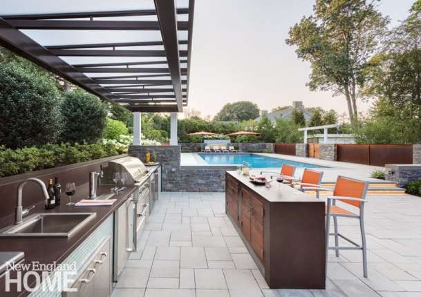 The full outdoor kitchen and bar are situated centrally for an ideal view of the pool.