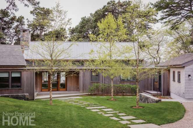 A path paved with native stone guides visitors to the front door of a seaside Cape Cod home that blends effortlessly into the natural environment.