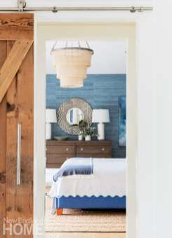Barn doors slide aside to reveal a master bedroom with a Mediterranean feel built around the bold Phillip Jeffries arrowroot wallcovering.