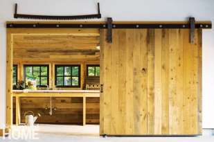 Vermont shingle style home potting shed with barn doors