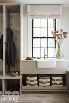 The chic mudroom incorporates a custom shade and a handy apron-front sink for washing hands.
