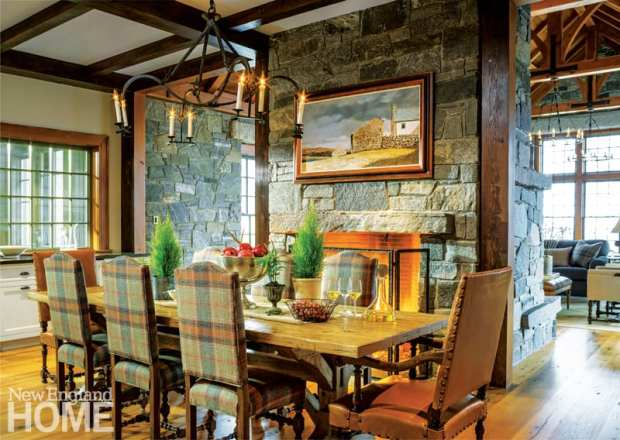 The rustic dining table is drawn close to the fireplace, its head chairs covered with caramel leather while the side chairs wear a subtle plaid.