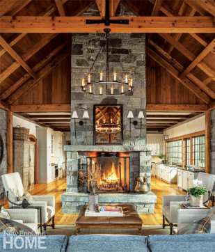 Local Vermont granite gives considerable heft to the great room, where a double-sided fireplace rises to a soaring peak in the living room.
