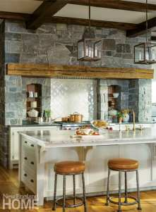The kitchen's attention-grabbing stone-clad wall is softened by a white tile backsplash; a heavy lintel beam is an example of the new use of old materials.