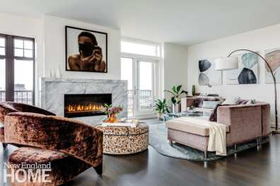 Lit fireplace in home with a modern painting featuring an African American woman hung above it