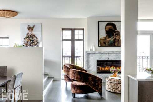 Wall separating dining room from office plus a view of the living room with a lit fireplace and modern artwork