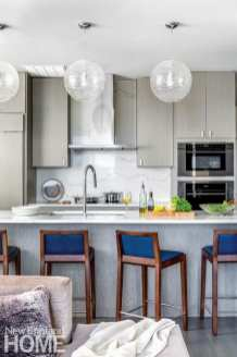 A view of the kitchen with a countertop bar featuring barstools with dark wood and blue upholstery