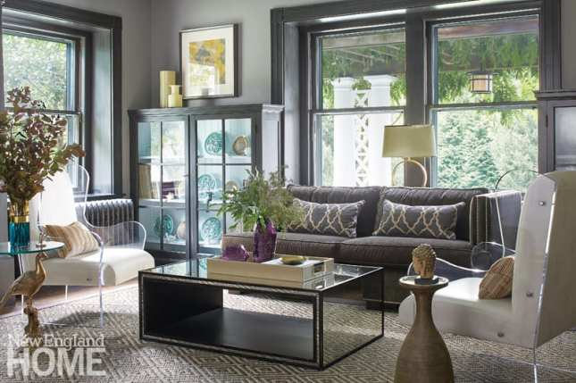 The formal living room featuring lucite side chairs, a gray couch, a display cabinet, a square coffee table and large windows with views of the yard