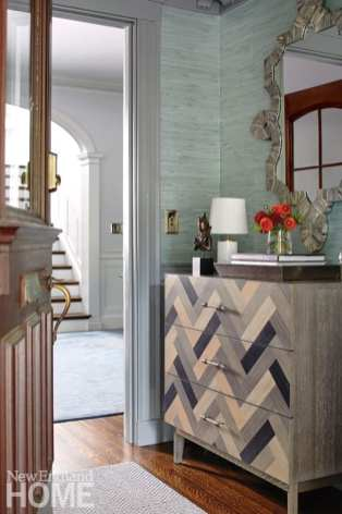 a chest of drawers in a chevron pattern of gray and neutral. There's a table lamp and a vase of orange flowers on top of the chest.