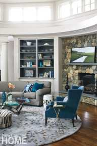 Family room featuring blue chair, gray couch with blue throw pillows, book shelves, stone fireplace, circular rug