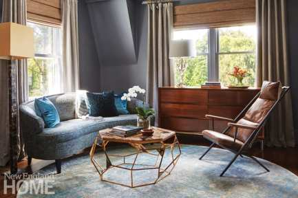 Sitting area with gray couch, brown leather chair, metal and stone coffee table, blue accent pillows, wood chest of drawers, window covered with taupe drapes
