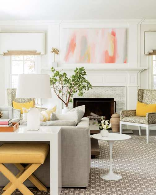 Living room with fireplace, light gray couch, white side table, leopard-print accent chair, tree, yellow bench and yellow accent pillows