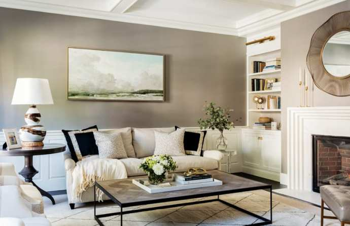 Living room with light gray couch, rectangular coffee table, abstract art above the couch and built in bookshelves