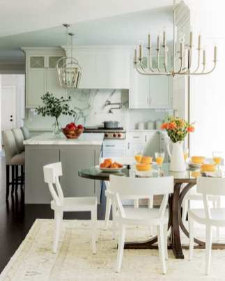 Cheerful kitchen with white cabinets, white chairs at the table, which is topped with a white pitcher filled with orange flowers