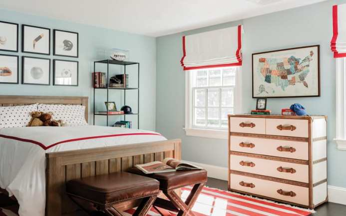 Child's bedroom with wood bed, bookshelves, chest of drawers and leather seats at the end of the bed