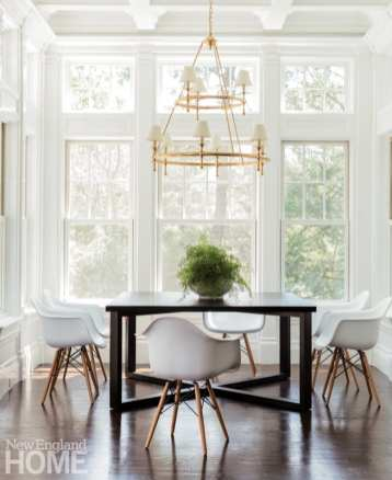 Bright dining area with large windows, black table and a brass and glass lighting fixture