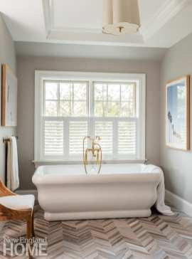 a large white bathtub with brass fixtures sits in front of a window. There's a photograph of palm trees on the gray wall.
