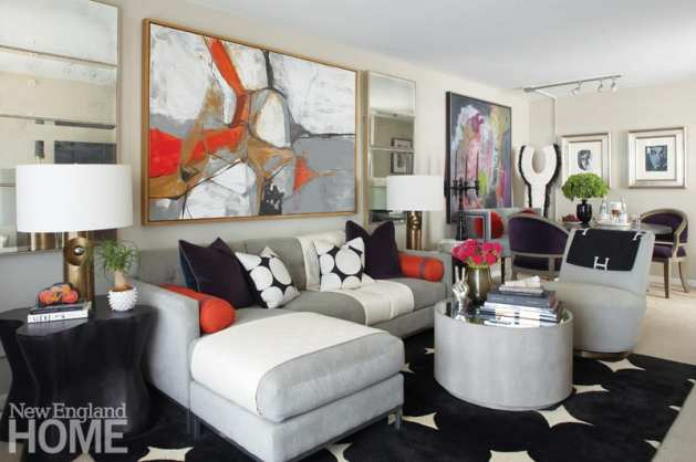The living room of designer Antonio Vergara features shades of black, white and gray with pops of orange accessories.