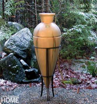 A gold-toned urn in an iron stand with boulders and trees in the background
