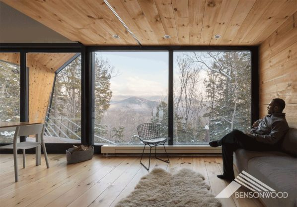 Living area of a cabin with wood-planked floors and a wood-planked ceiling. Floor-to-ceiling windows reveal a view of the surrounding mountains and trees.