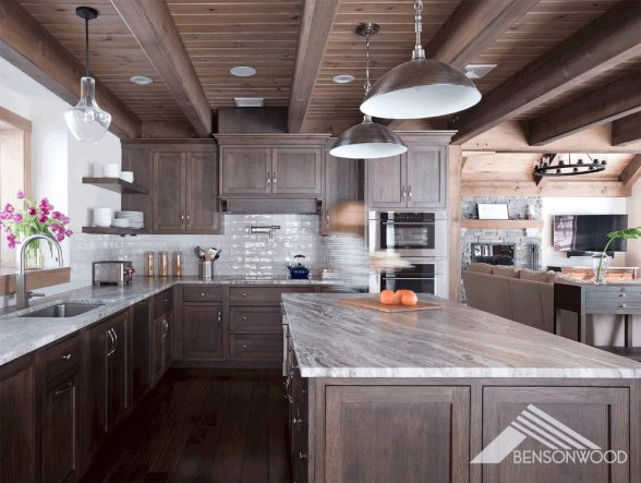 Kitchen with wood cabinets in a gray tone. The counters are white and gray marble. There's a blurry person walking through the photo. Two metal pendant lights hang above the counter.