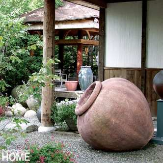 A reddish-colored urn turned on its side under an overhang. There's green foliage in the background.