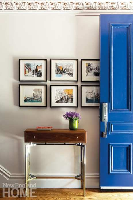 Blue door opens to an entryway featuring a brown side with an Hermes change tray and a vase of flowers. Above the table are six prints featuring Brooklyn scenes