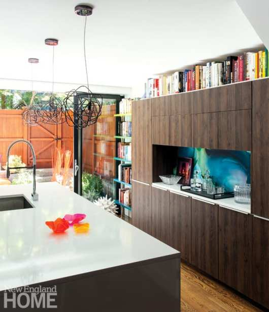 Kitchen with dark brown cabinets and white countertops. Cookbooks line the top shelf of the kitchen cabinets.
