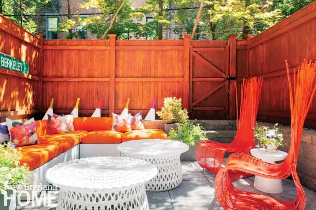 The back patio featuring an orange fence, orange high-backed chairs, a couch with orange cushions and three round white tables