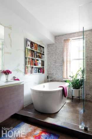 Master bathroom featuring stand alone bathtub, glass shower, potted plant and a photo of a bookcase above the bathtub.