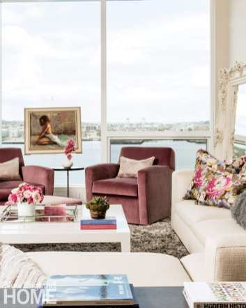 Living room in soft pastel colors with large windows looking out over Boston harbor. There's a painting floating on the window.