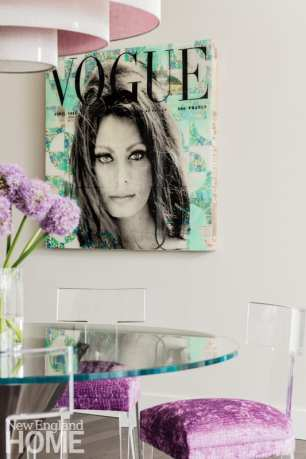 A painting of Sophia Loren on the cover of Vogue magazine hangs above a dining room table with purple chair cushions