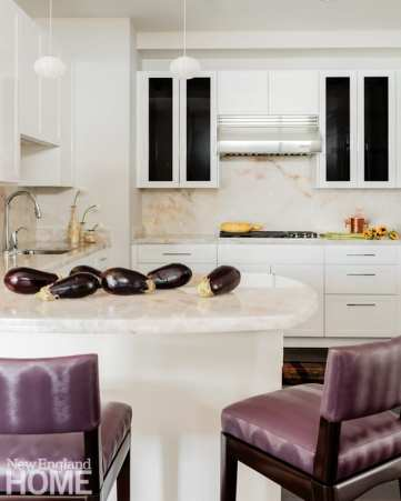 Looking into the kitchen we see white cabinets and an eat-in bar with bar stools covered in purple vinyl. There are eggplants on the white countertop.