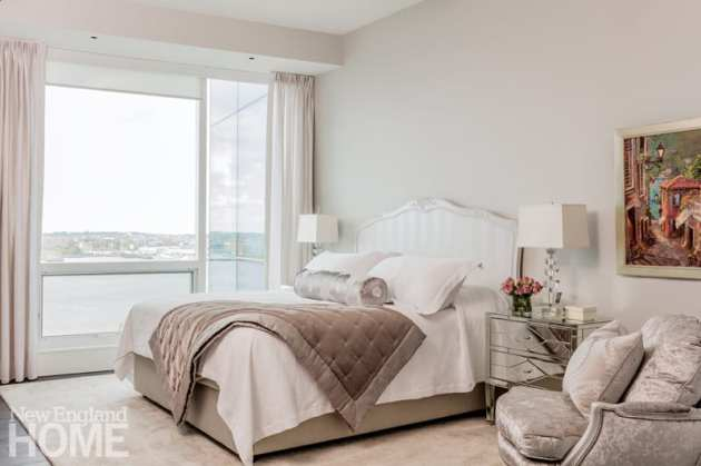 Master bedroom with bedding in shades of white and taupe. There's a view of Boston Harbor outside the window.