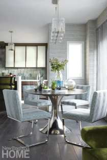 Dining room with round table and four chairs. It's near a window, and you can see into the kitchen. Everything is in shades of gray and we can see the corner of a green chair.