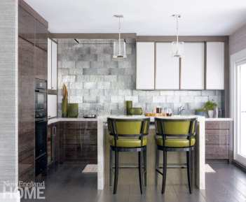 A view into a small kitchen with gray tile backsplash. There's a bar with two green barstools. Teo glass pendent lights hang above the bar.
