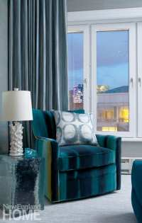 The master bedroom sitting area with a blue velvet armchair and a blue and white accent pillow. There's a window behind the chair and you can see the skyline.