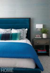 The master bedroom bed with a nightstand. The nightstand is topped with books, a barnacle and a plant